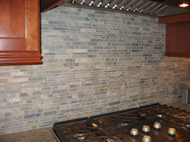 layered slate tiled backsplash with uba tuba granite
